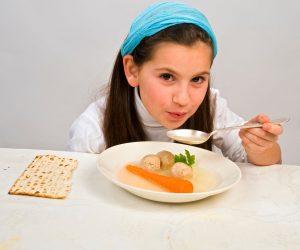 Young girl eating matzoh ball soup